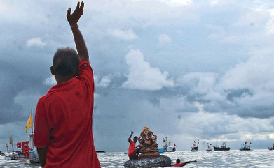 Man waving bye to Ganpati during immersion