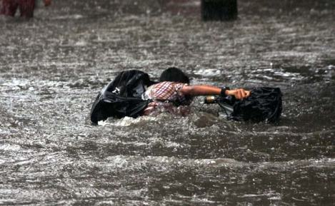 Schoolboy struggling in flooded street