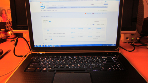 Dell Inspiron laptop with monitor showing Order Status.