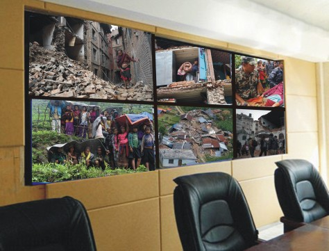 Deserted conference room with  video wall showing images of Nepal earthquake