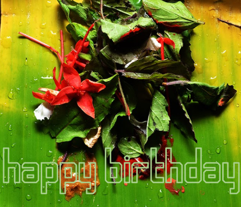 Piece of banana leaf with flowers and sandalwood paste. Happy birthday written on the leaf.